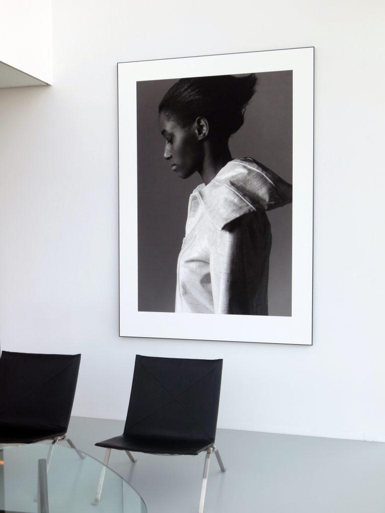 schwarz-weiss Bild einer Frau an einer weissen Wand