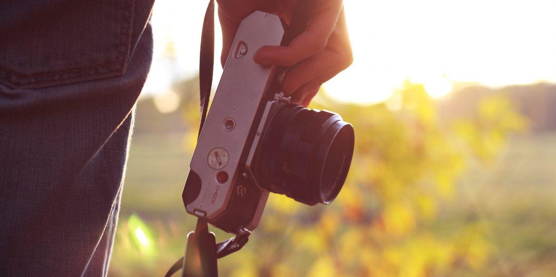 Mensch mit Kamera in der Hand in Abendstimmung