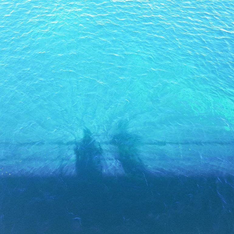 Schattenwurf zweier Personen in blauem Wasser