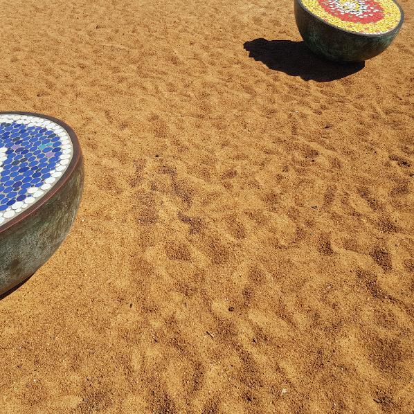orangefarbener Sand mit Mosaik-Kunst