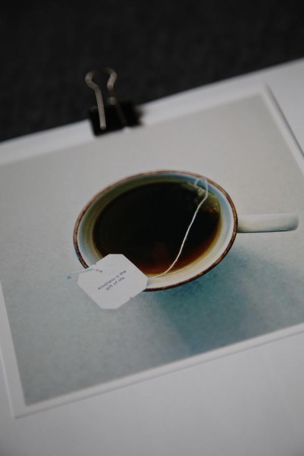 Detailaufnahme Square Print mit Tasse Tee, an weisses Blatte geheftet mit einer Klammer