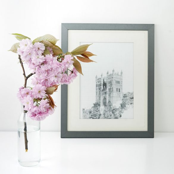 schwarz-weiss-Bild der Notre Dame in einem schwarzen Rahmen auf einem weissen Tisch mit einer Blüte im Vordergrund