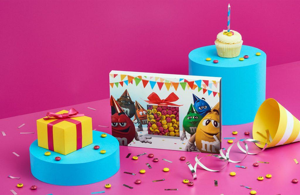 Schachtel mit bunten personalisierten M&Ms und Geburtstagsdekoration