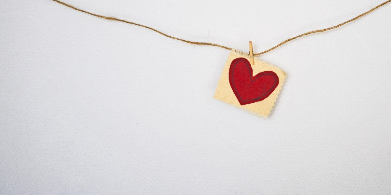 ein rotes genähtes Herz an einer Schnur an der Wand