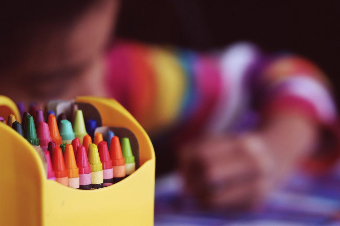 Kind malt mit Wachsmalstiften