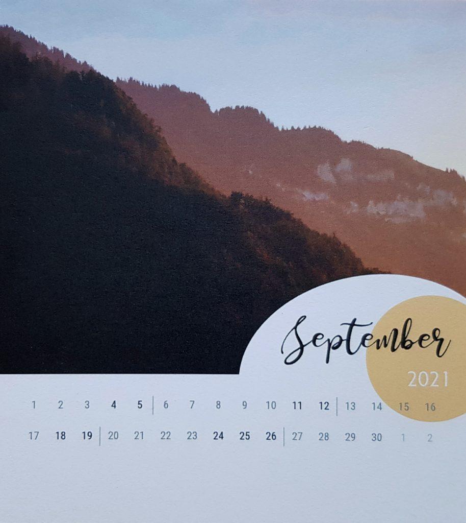 Kalenderseite mit Bild von Abendsonne auf einem Hügel