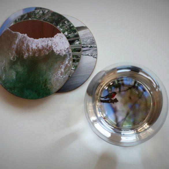 Blick von oben auf Untersetzer mit Fotos und Wasserglas