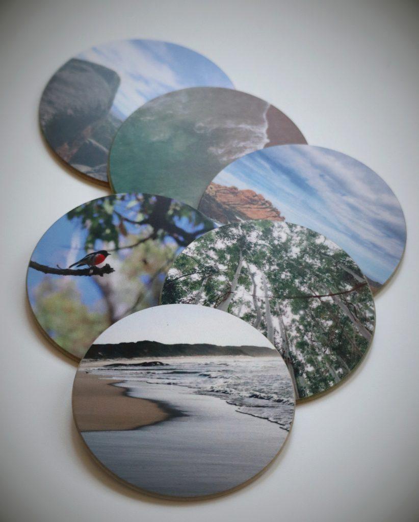 Mehrere Untersetzer mit Fotos in einer Reihe auf weissem Tisch
