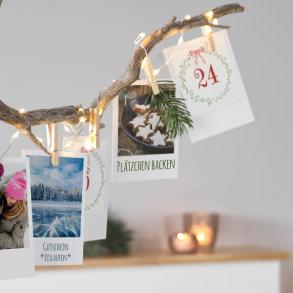 dekorierter Ast mit Adventskalender-Postkarten